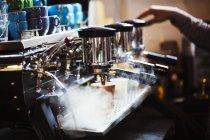 Человек, работающий за большой кофеваркой — стоковое фото
