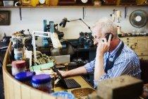 Clockmaker talking on the landline telephone — Stock Photo