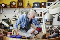 Clockmaker busy in his workshop. — Stock Photo