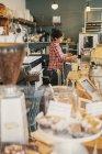 Femme dans une chemise à carreaux travaillant derrière le comptoir — Photo de stock