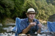 Man eating a grilled fish at picnic — Stock Photo