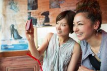 Japanese women looking at a cell phone — Stock Photo
