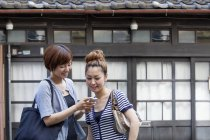 Japanese women looking at cellphone. — Stock Photo