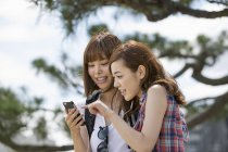 Japanese friends listening to music — Stock Photo