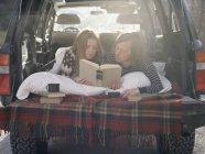 Coppia sdraiata nel retro della loro auto — Foto stock