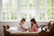 Sisters using a digital tablet. — Stock Photo
