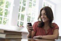 Frau, die ihr Smartphone überprüfen — Stockfoto