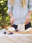 Woman cutting cheese on table — Stock Photo
