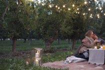 Couple assis sur le sol dans le verger de pommes — Photo de stock