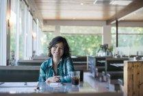 Жінка в зареєстрованого сорочки сидить за столом — стокове фото