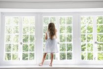 Female child standing at a window — Stock Photo