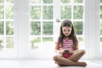 Mädchen hält Smartphone in der Hand. — Stockfoto