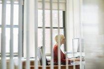 Женщина, сидя за столом с помощью компьютера — стоковое фото