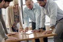 Businesspeople leaning over a digital tablet — Stock Photo
