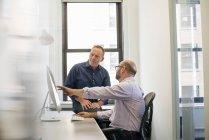 Compañeros de trabajo en una oficina hablando y refiriéndose - foto de stock