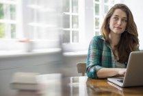 Donna con computer portatile in ufficio — Foto stock