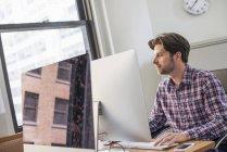 Людина за допомогою комп'ютера — стокове фото