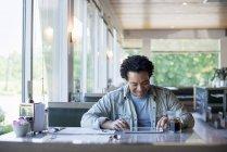 Homme dans une salle à manger à l'aide d'une tablette numérique — Photo de stock