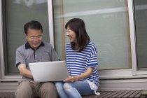 Чоловік і жінка, сидячи біля будинку — стокове фото