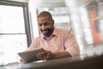 Homme assis à l'aide d'une tablette numérique — Photo de stock