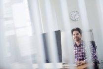 Mann sitzt an einem Schreibtisch — Stockfoto