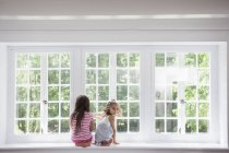 Sisters sitting by a large window. — Stock Photo