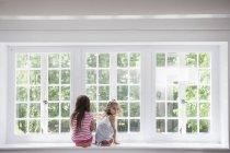 Hermanas sentadas junto a una gran ventana . - foto de stock