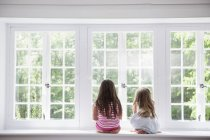 Two girls sitting by a large window. — Stock Photo