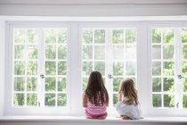 Zwei Mädchen sitzen an einem großen Fenster. — Stockfoto