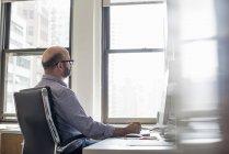 Людина в офісі, за допомогою комп'ютера — стокове фото