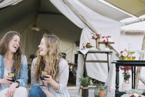 Women laughing and sitting outside a tent — Stock Photo