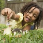 Girl stroking the head of a duckling — Stock Photo