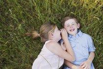 Bruder und Schwester liegen auf dem Rasen — Stockfoto