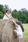 Girls playing by a large haybale — Stock Photo