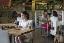 Mujer sentada en la mesa de café - foto de stock