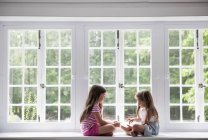 Girls sitting on windowsill — Stock Photo