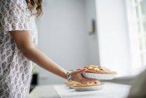 Женщина, перевозящие продовольствие на стол — стоковое фото