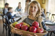 Girl carrying apples — Stock Photo