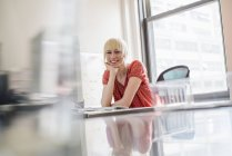 Woman sitting at an office desk — Stock Photo