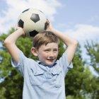 Junge hält einen Fußball — Stockfoto