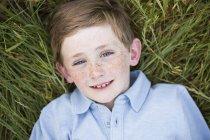 Мальчик лежит на траве . — стоковое фото