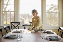 Girl setting the table with plates — Stock Photo