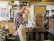 Antique furniture restorer in his workshop — Stock Photo