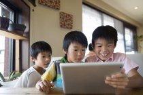 Boys looking at digital tablet — Stock Photo