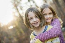Dos chicas sonrientes en el bosque - foto de stock