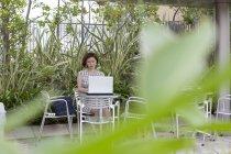 Mujer usando un ordenador portátil en la cafetería - foto de stock