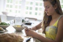 Девушка проверяет свой смартфон — стоковое фото