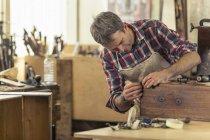 Antique furniture restorer working — Stock Photo