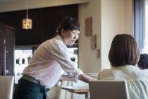 Жінка порції офіціанткою в кафе — стокове фото