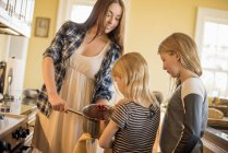 Woman with two children holding cooking pot — Stock Photo